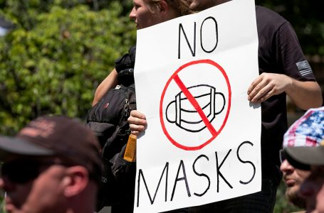 """An anti-mask protestor holds up a sign in front of the Ohio Statehouse during a right-wing protest """"Stand For America Against Terrorists and Tyrants"""" at State Capitol on July 18, 2020 in Columbus, Ohio. – Protestors descended on Columbus, Ohio for a planned anti-mask rally in response to local laws requiring people to wear a mask in many Ohio cities. (Photo by Jeff Dean / AFP) (Photo by JEFF DEAN/AFP via Getty Images)"""